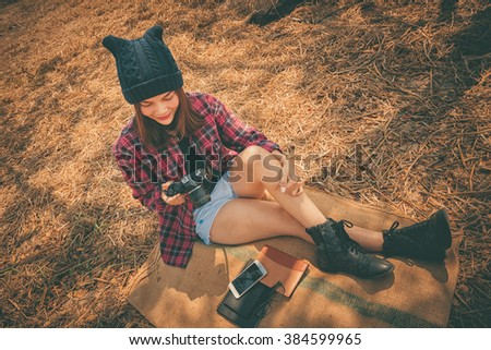 young woman sitting on hay with vintage camera