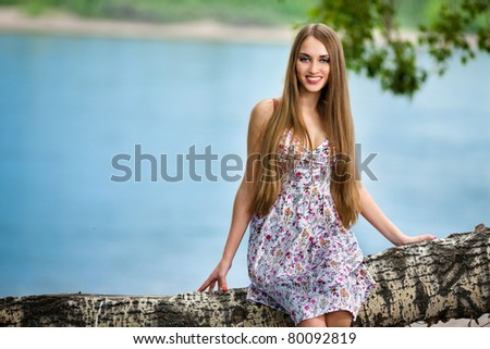 Young woman sitting on log in the park near the river - stock photo