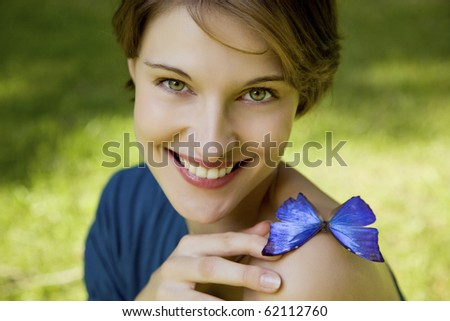 young woman sitting on meadow joyfull playing with butterfly - stock photo