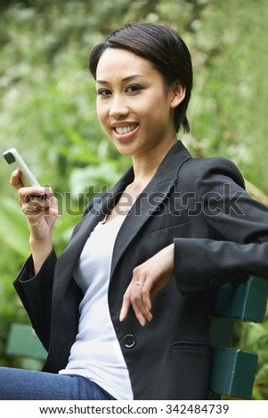 Young Woman Sitting On Park Bench Reading Text Message