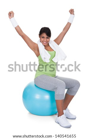 Young Woman Sitting On Pilates Ball With Arm Raised Over White Background - stock photo