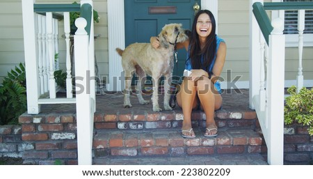 Young woman sitting on porch with her dog - stock photo