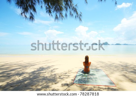 Young woman sitting on sand and looking to a sea - stock photo