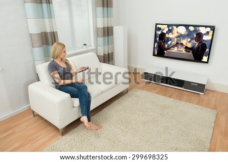 Young Woman Sitting On Sofa Watching Movie In Living Room - stock photo