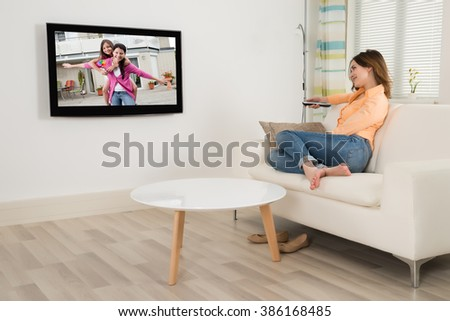 Young Woman Sitting On Sofa Watching Television In Her Room