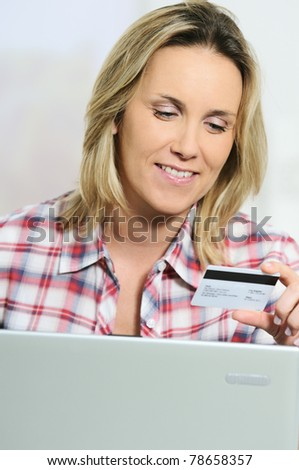 Young woman sitting on sofa with computer and credit card