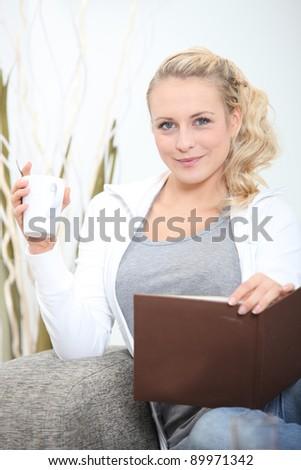 young woman sitting on sofa with photograph album and mug of coffee - stock photo
