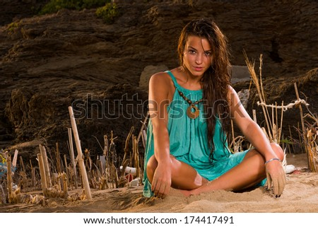 Young woman sitting on the beach - stock photo
