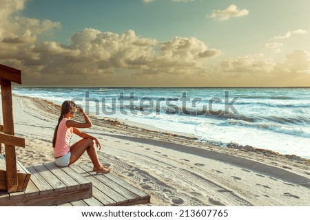 young woman sitting on the beach and enjoying amazing sunrise - stock photo