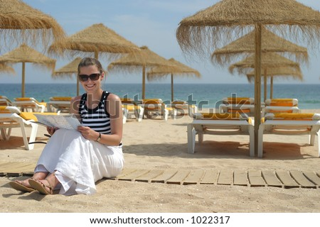 Young woman sitting on the beach and reading the map. - stock photo