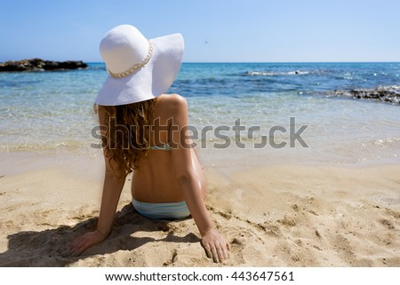 Young woman sitting on the beach. Portrait of a girl in white hat relaxing on the beach. Beautiful Summer sea side beach with turquoise water. View from behind - stock photo