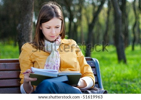 young woman sitting on the bench and reading book - stock photo