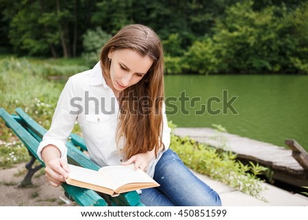 Young woman sitting on the bench in a park and reading a book. Beautiful european girl studying a subject with book