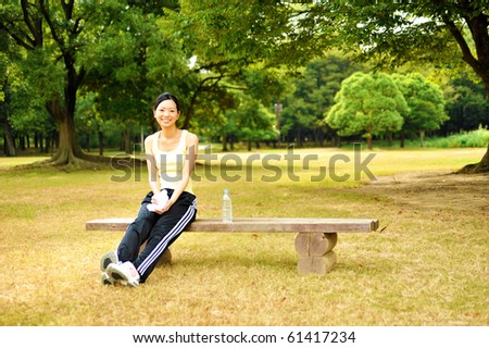 young woman sitting on the bench in the park