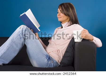Young woman sitting on the black sofa with a cup and a book in her hands; blue background, in studio. - stock photo
