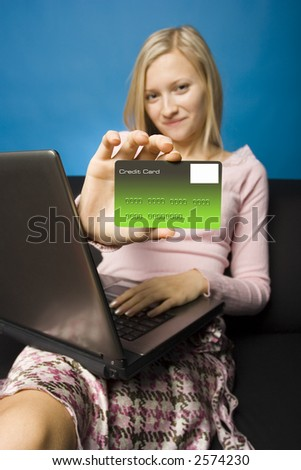 Young woman sitting on the black sofa with laptop and credit card in her hand. Focus on the card. Face unfocus. - stock photo