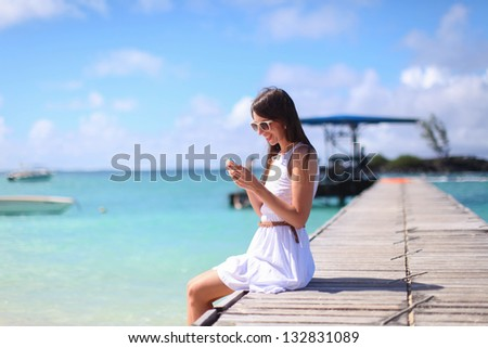 Young woman sitting on the bridge and talking on her phone - stock photo
