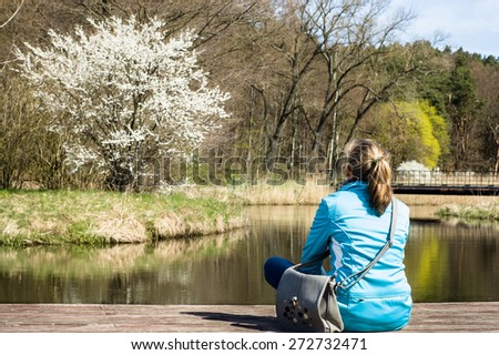 Young woman sitting on the bridge by the river and looks at a flowering tree, view from behind, relaxing at leisure, beautiful spring landscape and nature background