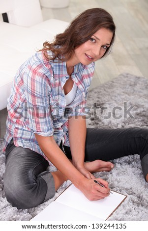 young woman sitting on the carpet and writing - stock photo