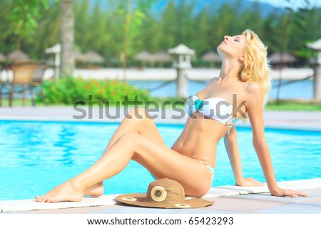 Young woman sitting on the edge of swimming pool - stock photo