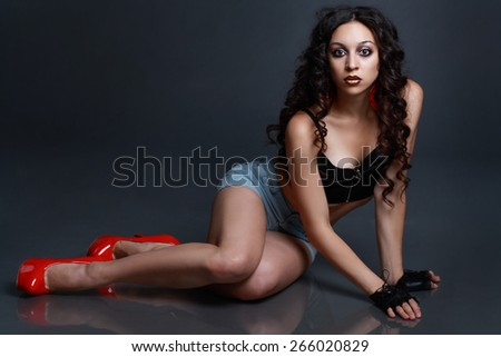 young woman sitting on the floor against black background