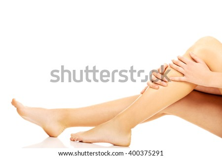 Young woman sitting on the floor and touching her legs