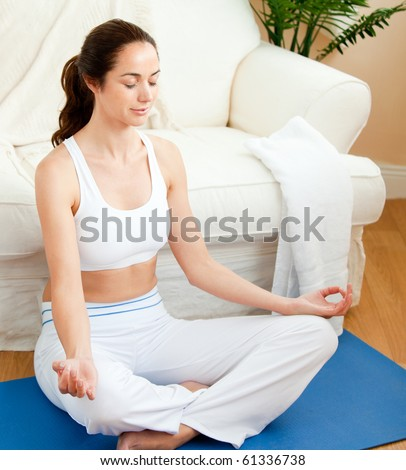 Young woman sitting on the floor doing yoga in her living room - stock photo