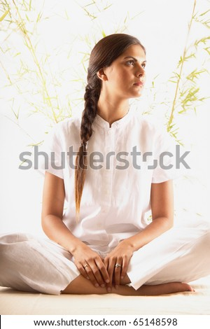 Young woman sitting on the floor meditating - stock photo