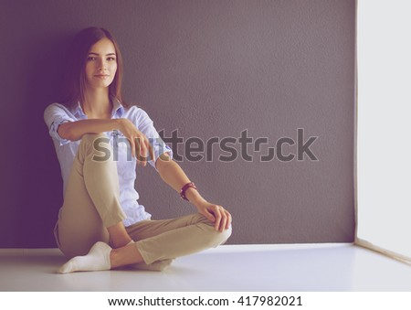 Young woman sitting on the floor near dark wall - stock photo