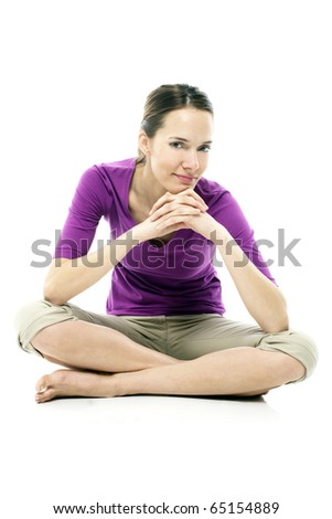 Young woman sitting on the floor on white background studio - stock photo
