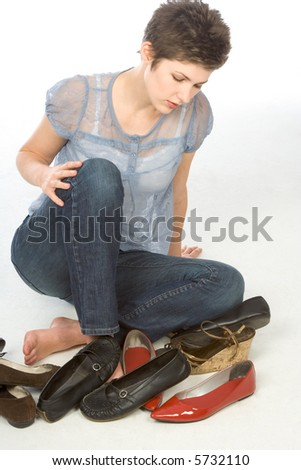 Young woman sitting on the floor tries to choose pair of shoes