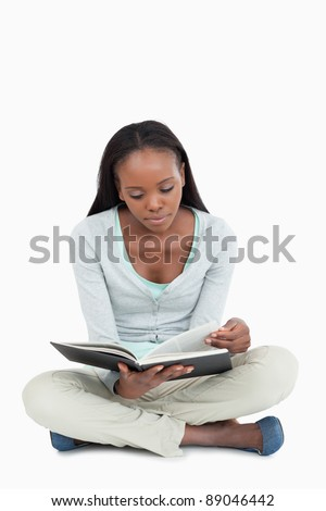 Young woman sitting on the floor turning the page of her book against a white background