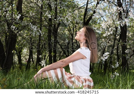 Young woman sitting on the grass in the lush garden and enjoy the sun. Spring portrait in nature - stock photo