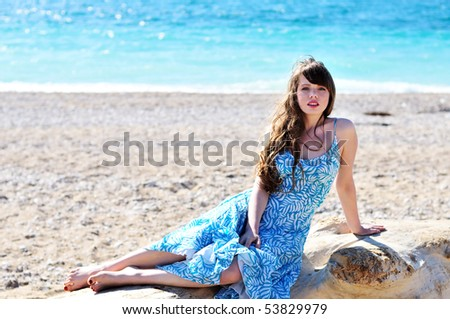young woman sitting on the log on the beach - stock photo