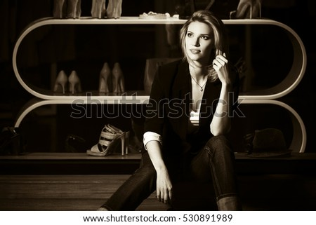 Young woman sitting on the mall window Female stylish fashion model in night outdoor