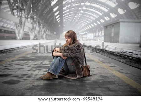 Young woman sitting on the platform of a train station - stock photo