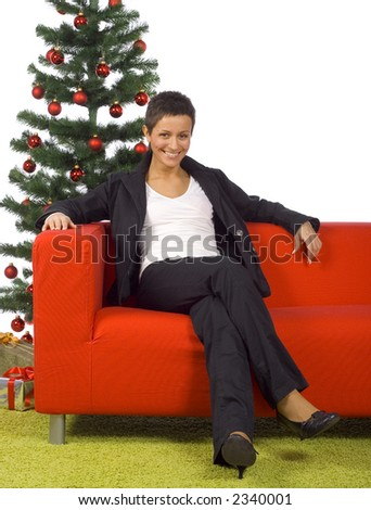 young woman sitting on the red sofa with chritmas tree behid her - stock photo