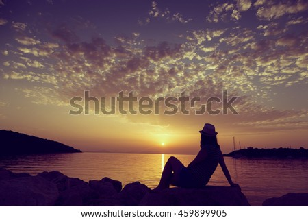Young woman sitting on the rocky shore, wearing hat and enjoying a beautiful sunset in Syvota bay, Greece - stock photo
