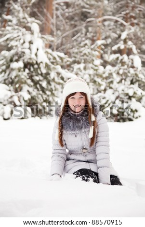 Young woman sitting on the  snow in winter