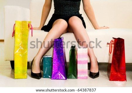 young woman sitting on the sofa with shopping bags - stock photo