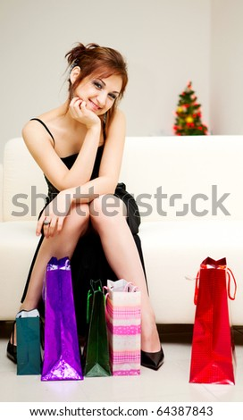 young woman sitting on the sofa with shopping bags