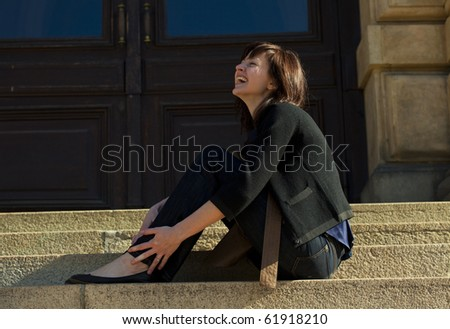 young woman sitting on the steps - stock photo