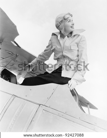 Young woman sitting on top of a biplane with gargles and hat - stock photo