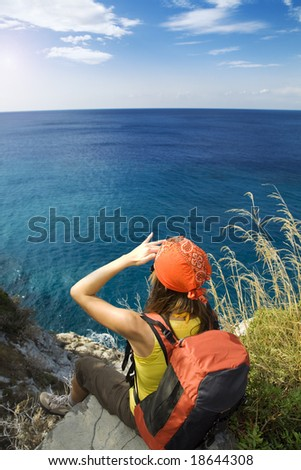 young woman sitting on top of a cliff and looking up to the sky - stock photo