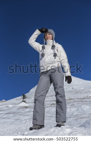 Young woman sitting on top of a snowy mountain admiring the view