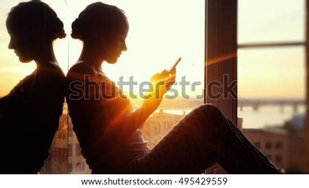 Young woman sitting on window uses smart phone  background of the sunset and city