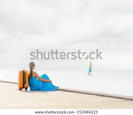 Young woman sitting on wooden pier.