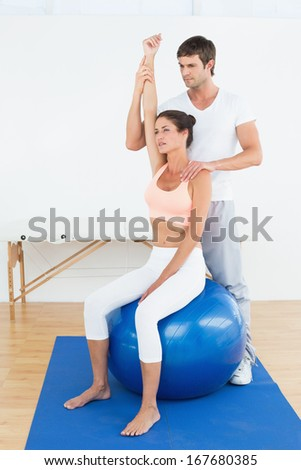 Young woman sitting on yoga ball while working with a physical therapist - stock photo