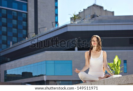 young woman sitting outdoors in yoga pose, near - green flower, on modern building background - stock photo