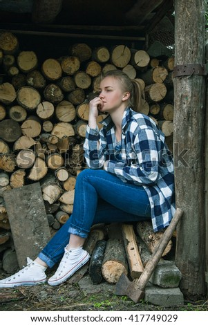 Young woman sitting outdoors on the background of stacked firewood and thinking - stock photo